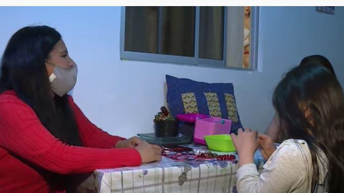 niña con síndrome de Down y su mamá hacen manillas para comprar útiles escolares.jpg