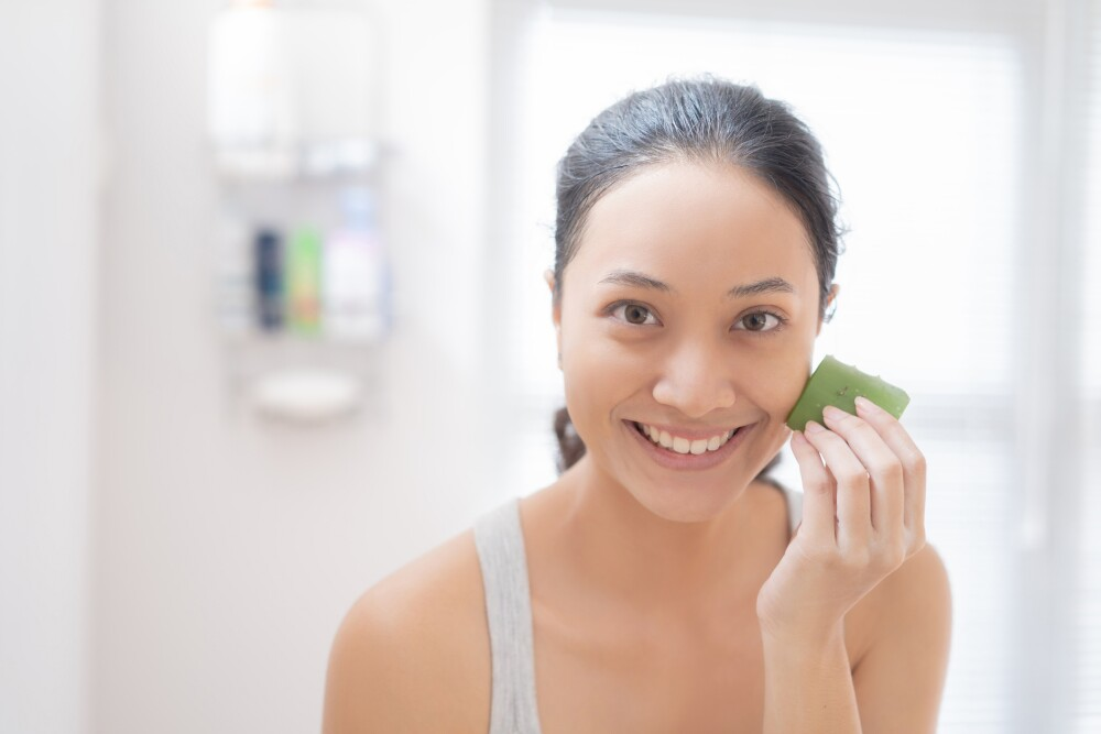 Asian woman Apply aloe vera to her face in the bathroom.