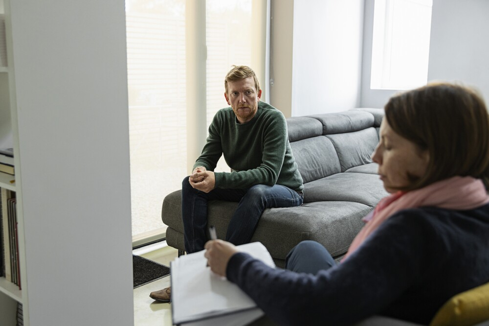Man with mental health issues sits on sofa and talks to his therapist