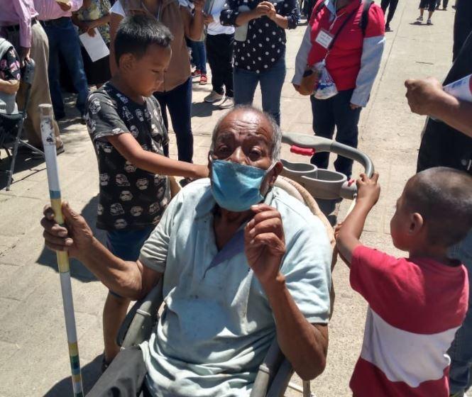 niños llevan a vacunar a abuelo en coche de bebé