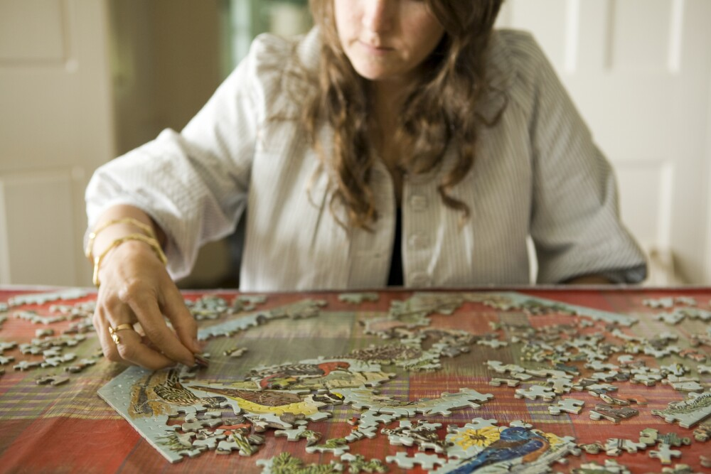 Woman doing jigsaw puzzle in home