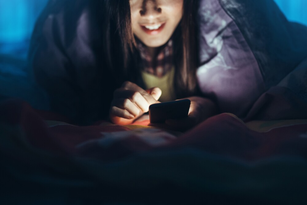Woman texting on smartphone under the bed sheets