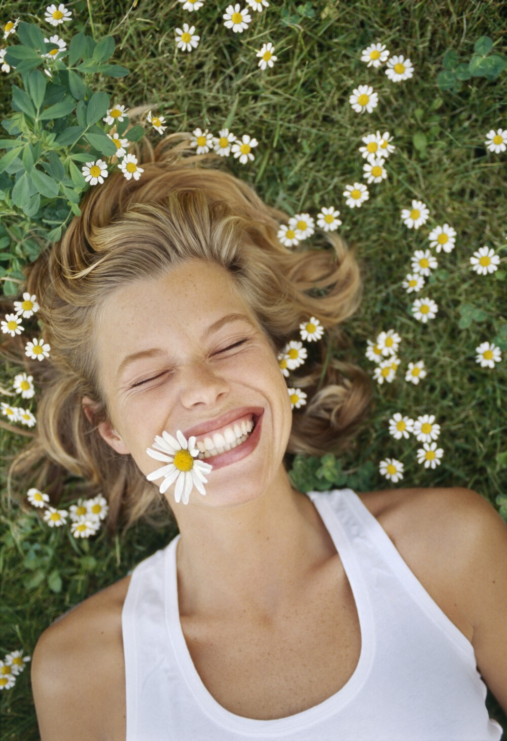 Young woman lying on grass, with daisy in mouth, smiling