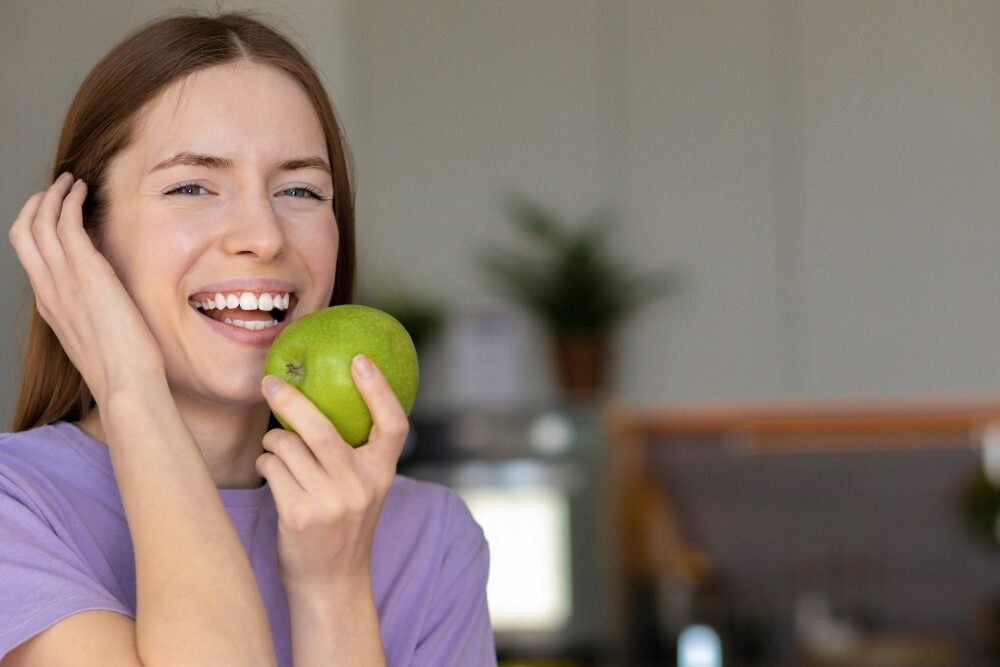 Beautiful caucasian woman with white teeth smiling and eating a green apple, healthy lifestyle