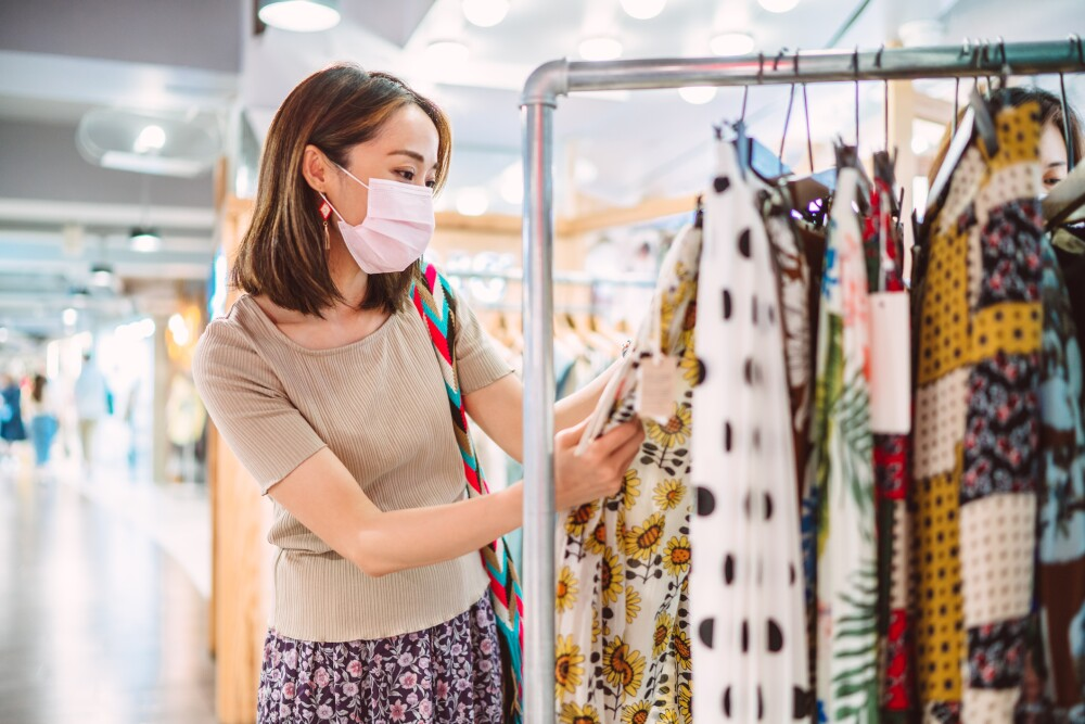 Young Asian woman in protective face mask shopping for clothing in a fashion boutique