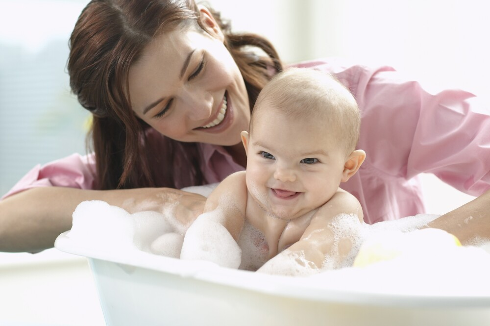 Mother with baby girl (6-9 months) in bath tub, smiling