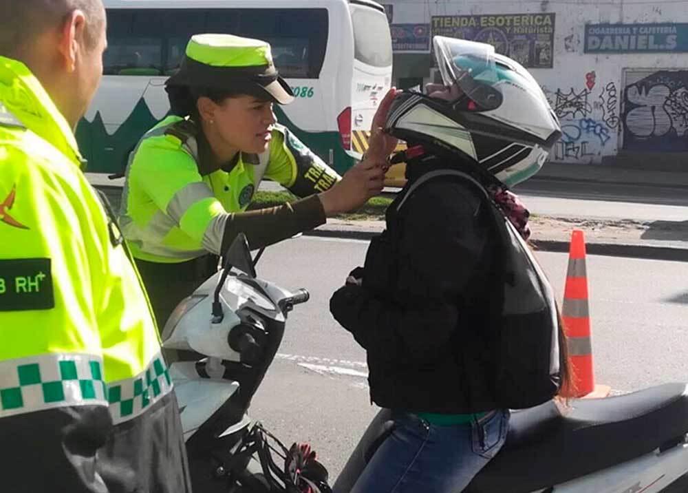 Agente de policía inspeccionando el uso del casco en Bogotá