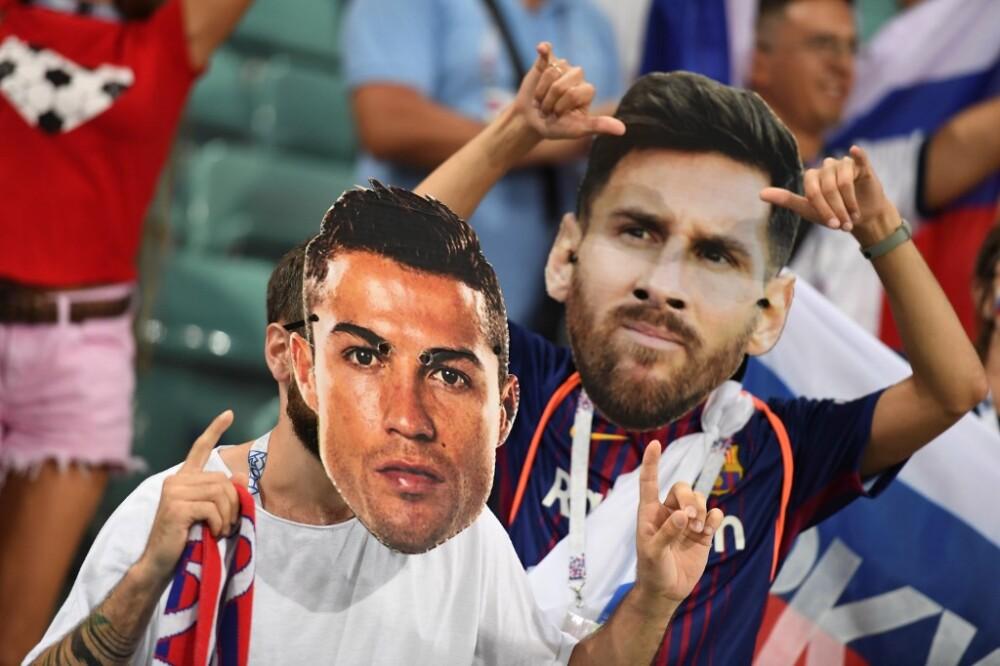 Hinchas con máscaras de Cristiano Ronaldo y Lionel Messi