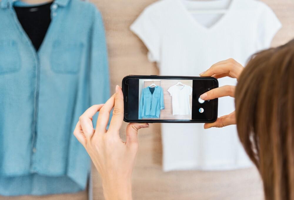 Woman taking photo of denim shirt white basic t-shirt on smartphone