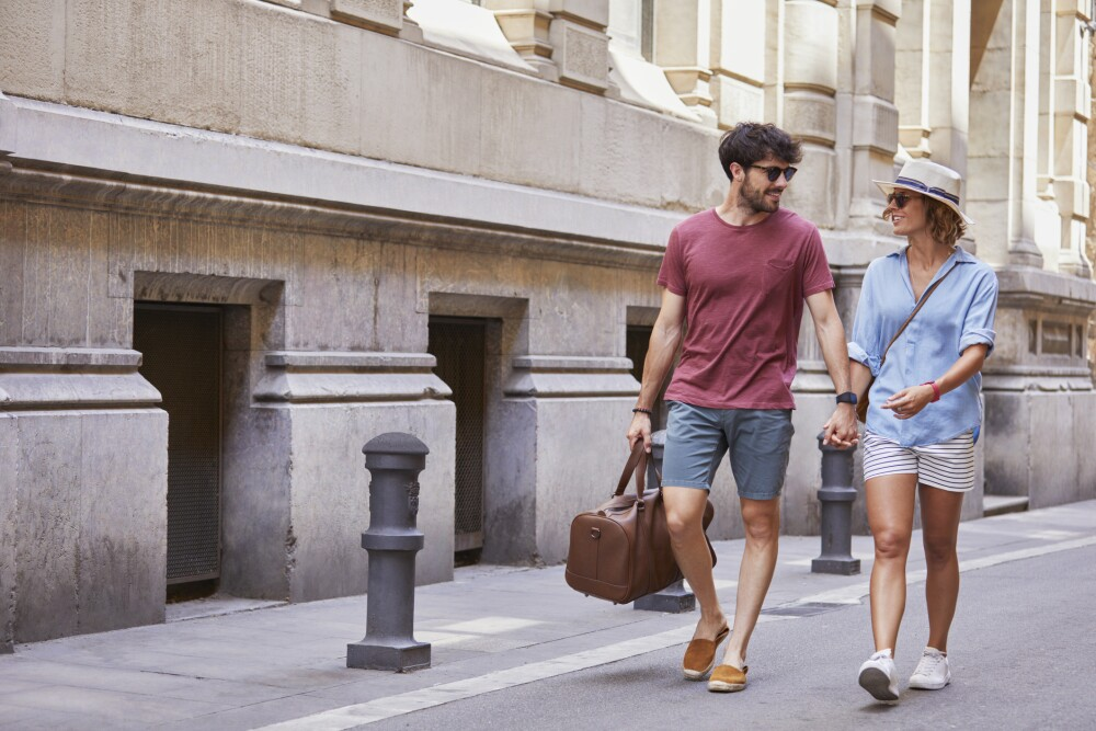 Smiling couple walking with luggage on street in Barcelona