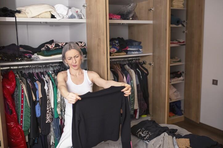 Woman reorganizing her wardrobe in her bedroom
