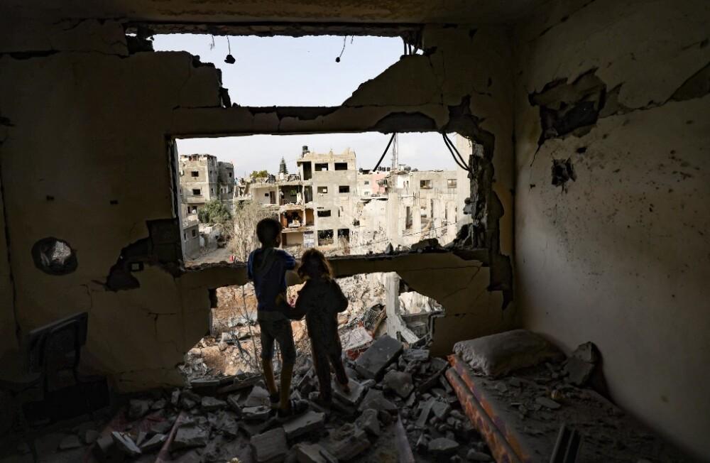 Niños palestinos en medio de destrozos de bombardeo israelí en Gaza.jpeg