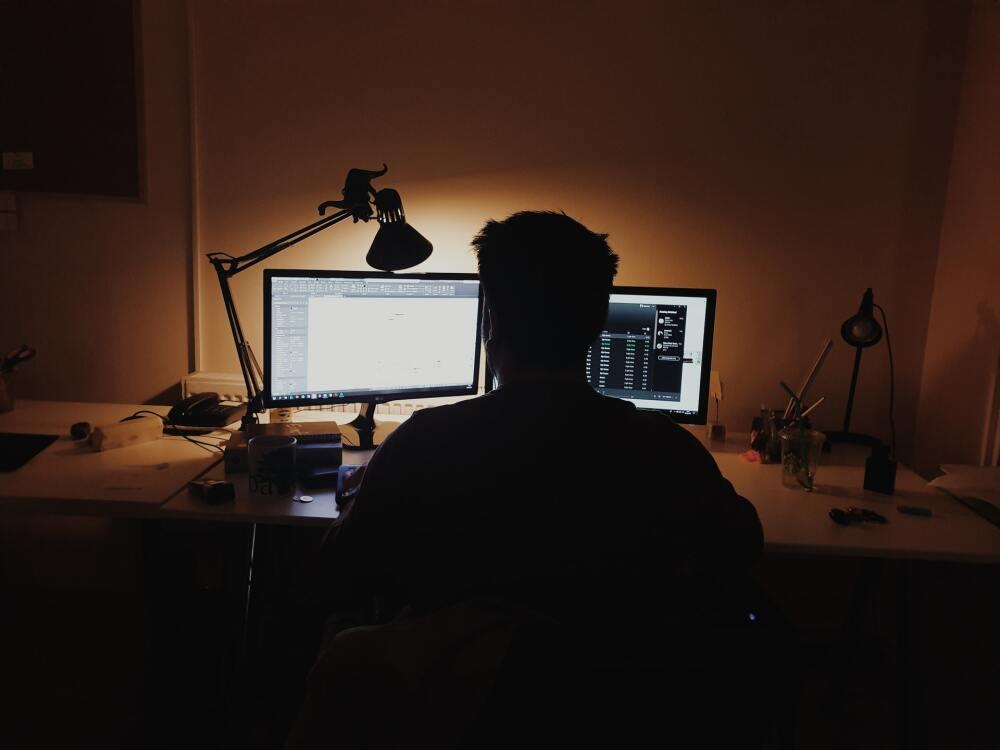 Hombre delante de dos pantallas de computador.