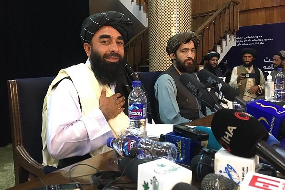 Zabihullah Mujahid (izq.), vocero de los talibanes en Afganistán