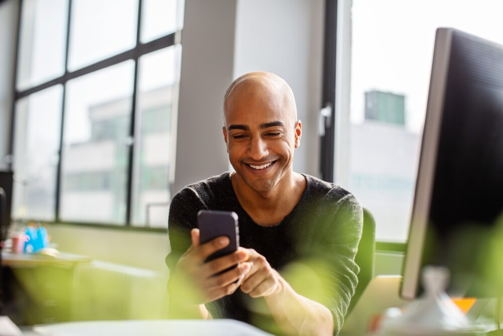 Smiling mid adult man using phone at his desk