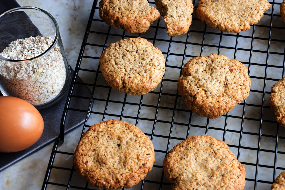 Glutenfree homemade oatmeal cookies, oats, egg on cooling rack. Selective focus. Toned photo